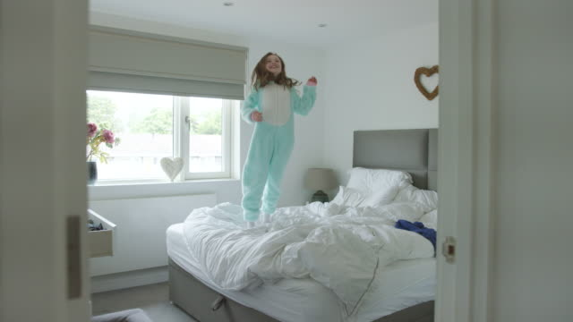 young girl jumping on parents' bed - only girls stock videos & royalty-free footage