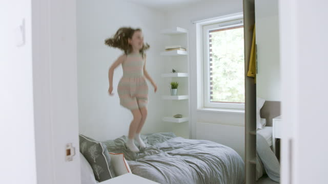 young girl jumping on parents' bed - child stock videos & royalty-free footage