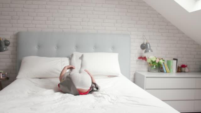 stockvideo's en b-roll-footage met een jong meisje springen op en neer op haar bed en lachen - 2 3 jaar