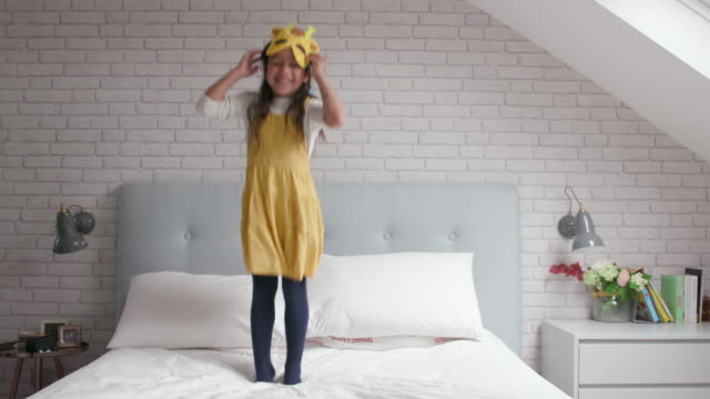 a young girl jumping up and down on her bed - yellow stock videos & royalty-free footage