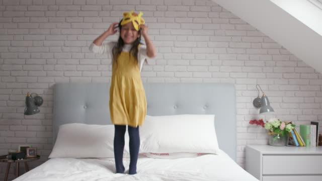 ein junges mädchen springt auf und ab auf ihrem bett - vertrauen stock-videos und b-roll-filmmaterial