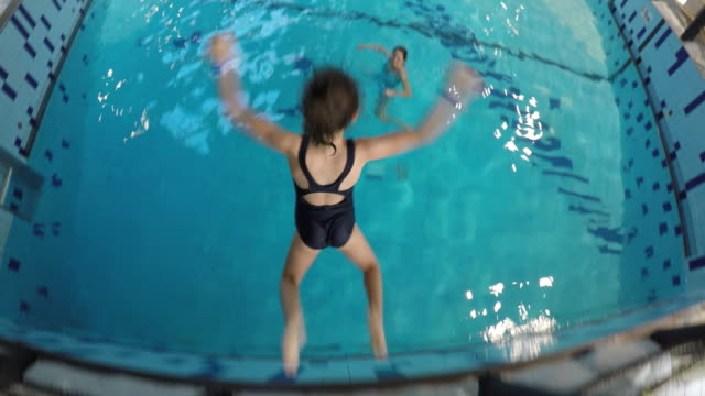 Young girl jumps from a high edge into a swimming pool
