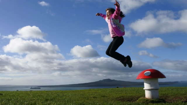 Young girl jumps over magic mushroom