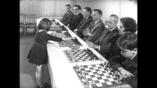 young girl jutta hempel plays chess at local competition in flensburg, west germany / six year old hempel looks serious as she plays against several... - scacchi video stock e b–roll