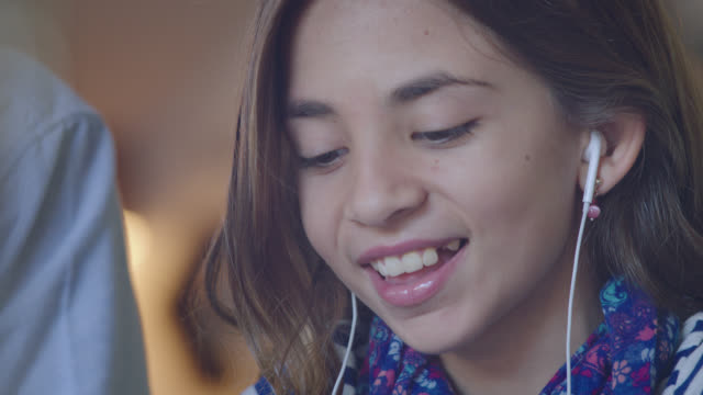 CU. Young girl laughs and plays on smartphone with headphone earbuds in.