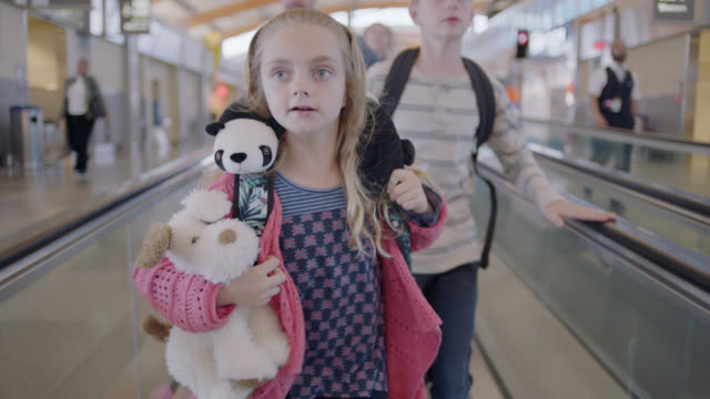 young girl leads family of four down moving walkway as they run through airport terminal. - familie mit zwei kindern stock-videos und b-roll-filmmaterial