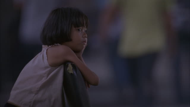 a young girl leans on a chair on a sidewalk. - poverty stock videos & royalty-free footage