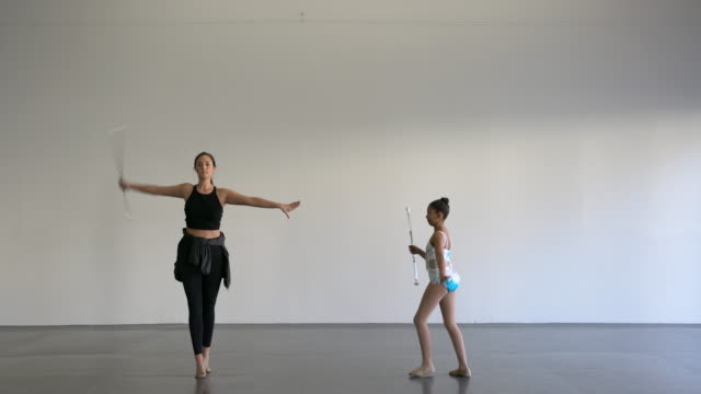 stockvideo's en b-roll-footage met ws young girl learning a dance routine with a twirling baton - gympak