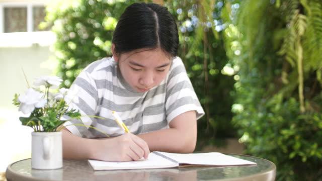 vidéos et rushes de jeune fille apprenant et écrivant au sujet de la nouvelle salle de classe due à la quarantaine à la maison - seulement des petites filles
