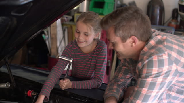 cu young girl learning from her father how to fix a car engine. - checked pattern stock videos & royalty-free footage