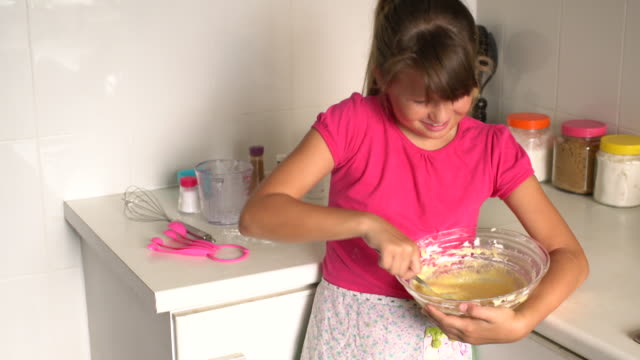 MS young girl learning how to bake at home.