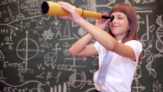 stockvideo's en b-roll-footage met jong meisje leren spelenderwijs in frot van een groot schoolbord met telescoop - verrekijker