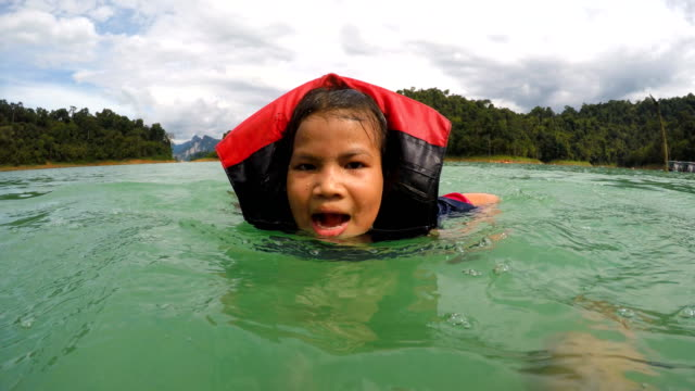 4k: unga flickan lär sig att simma i dammen - utebassäng bildbanksvideor och videomaterial från bakom kulisserna