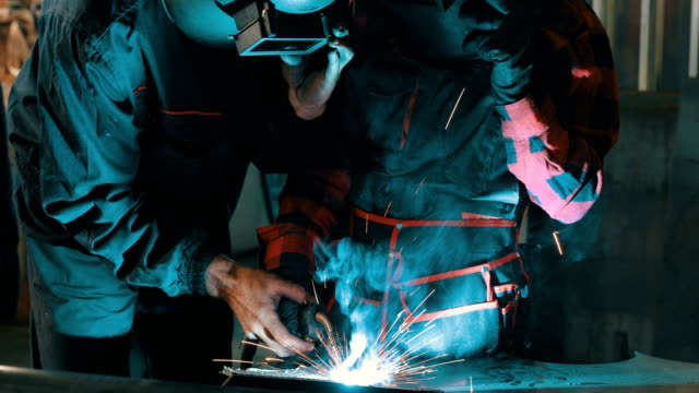 Young girl learns to using a welding machine