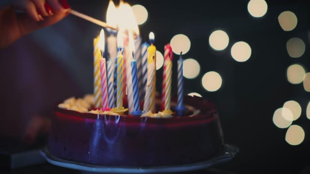 young girl lighting 16 candles on birthday cake - compleanno video stock e b–roll
