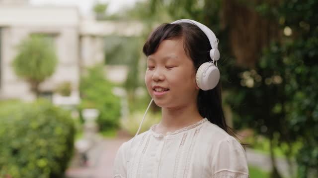 vídeos de stock, filmes e b-roll de uma rapariga que escuta a música em um parque público em formosa - olhos fechados