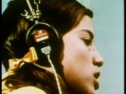 vídeos y material grabado en eventos de stock de 1969 cu zo young girl listening with headphones and repeating words during hearing test/ usa/ audio - sordera