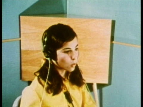 1969 ms young girl listening with headphones in isolation chamber and repeating words during hearing test/ usa/ audio - repetition stock videos & royalty-free footage