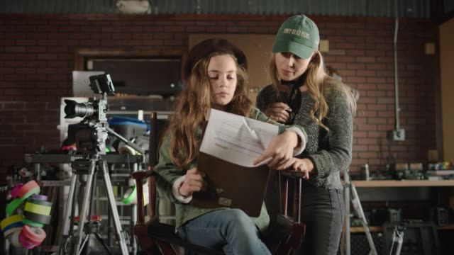 slo mo. young girl living her dream as a movie director discusses the shooting script with the female filmmaker on a film set. - daydreaming stock videos & royalty-free footage