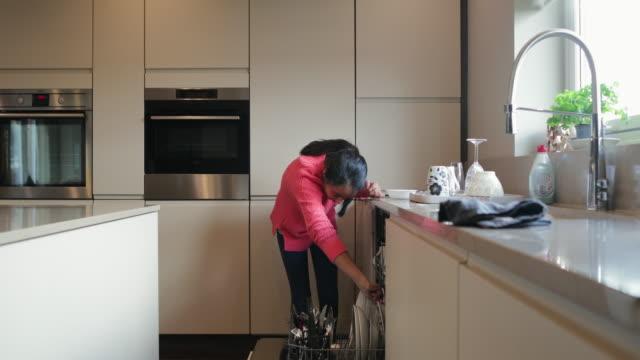 junges mädchen, das die spülmaschine lädt - home sweet home englische redewendung stock-videos und b-roll-filmmaterial