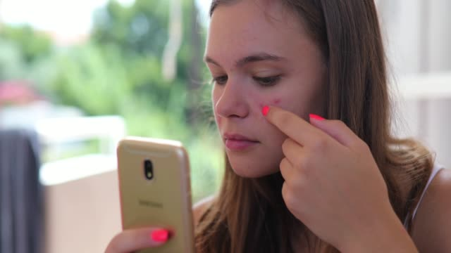 young girl looking at her front camera on mobile phone, and she's sad about her acne problem - worried stock videos & royalty-free footage