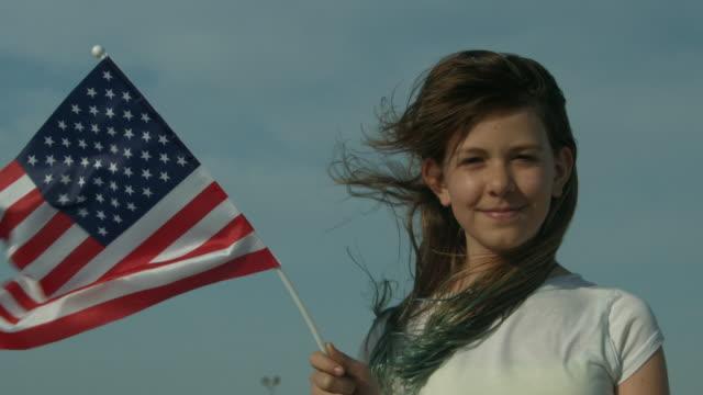 a young girl looking towards camera holding an american flag outside in new york city in slow motion - endast en tonårsflicka bildbanksvideor och videomaterial från bakom kulisserna