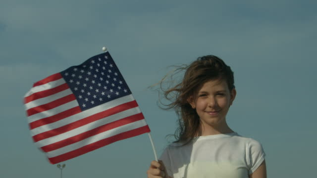A young girl looking towards camera holding an American flag outside in New York City in slow motion