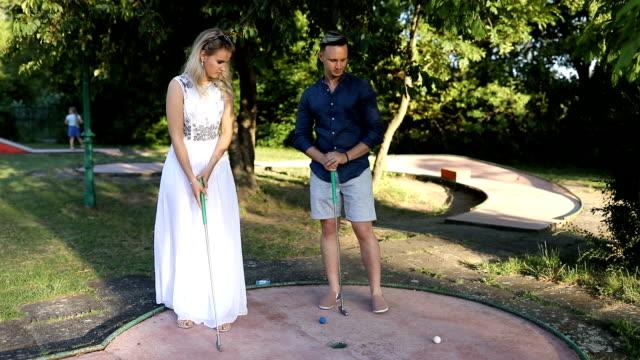 若い女の子はミニゴルフでの勝利について幸せに見えます - ゴルフ点の映像素材/bロール