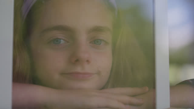 young girl looks through a window and into the camera - green background stock videos & royalty-free footage