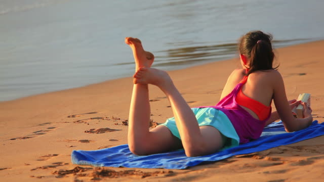 Young girl lying on tropical beach reading book