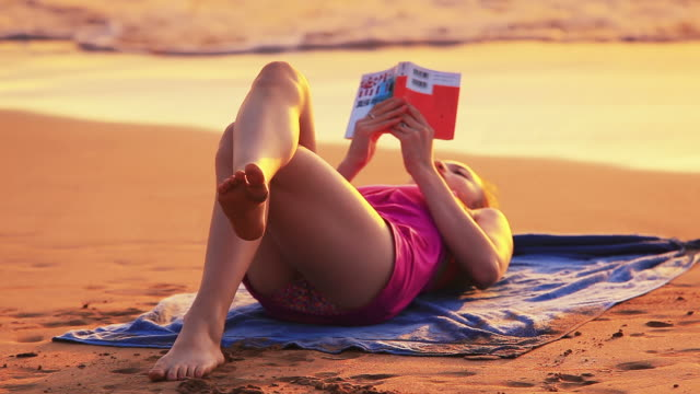 young girl lying on tropical beach reading book - human toe stock videos and b-roll footage