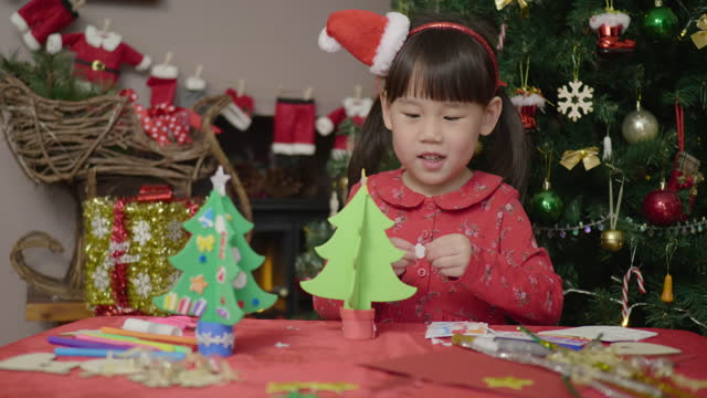 young girl making christmas craft in front of christmas tree - decoration stock videos & royalty-free footage