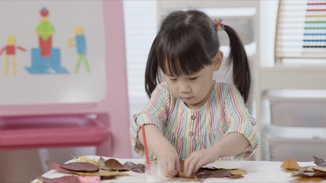vídeos de stock e filmes b-roll de young girl making craft using autumn leaves at home - craft