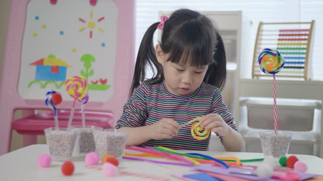 young girl making lollipop craft using pipe cleaner at home - lollipop stock videos & royalty-free footage