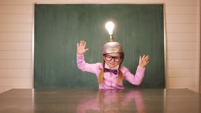 vídeos de stock e filmes b-roll de young girl nerd uses thinking cap for big idea - light bulb