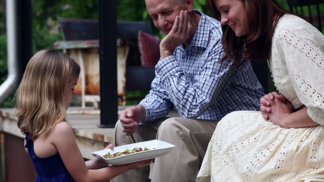 TU young girl offering appetizers to mother and grandfather on front porch of home