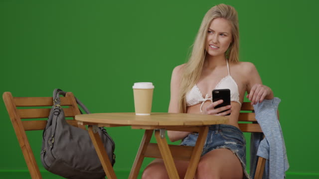 young girl on her smart phone at a caf_ table in her bikini top on green screen - bikini top stock videos & royalty-free footage