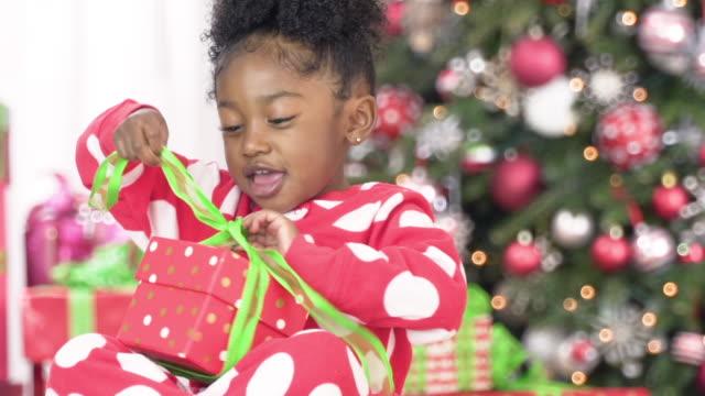 young girl opening christmas present - weihnachtsgeschenk stock-videos und b-roll-filmmaterial