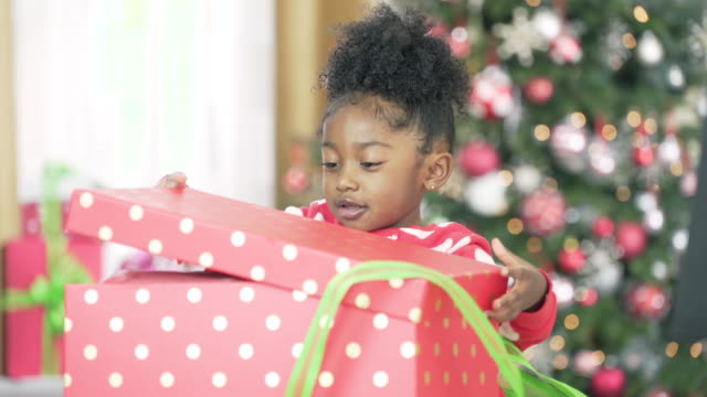 young girl opening christmas present - wrapping paper stock videos & royalty-free footage