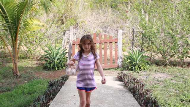vidéos et rushes de young girl opens gate and walks through carrying a batch of eggs in an egg holder - kelly mason videos