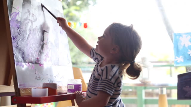 vídeos y material grabado en eventos de stock de a young girl painting at a easel inside of a home. - descubrimiento
