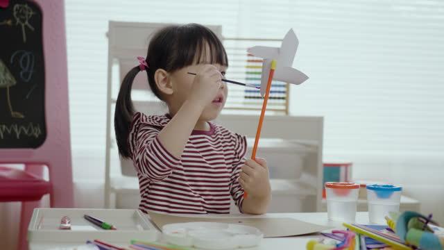 自宅で彼女の風車の工芸品を描く若い女の子 - 接着のり点の映像素材/bロール