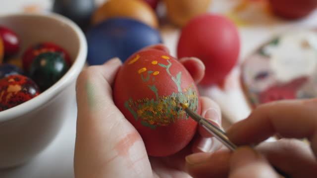 vídeos de stock e filmes b-roll de young girl painting on easter eggs - domingo de páscoa