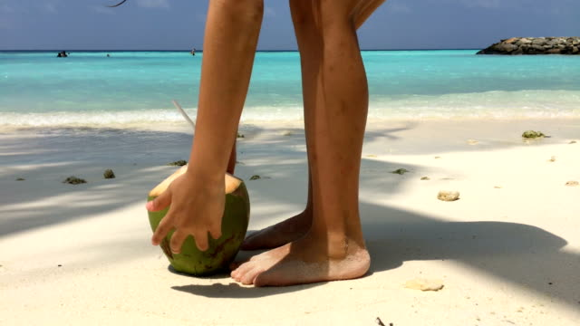 young girl picking up coconut drink on tropical island's beach - tropical drink stock videos & royalty-free footage