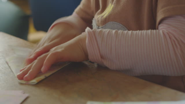 vídeos de stock e filmes b-roll de young girl playing at home. - origami
