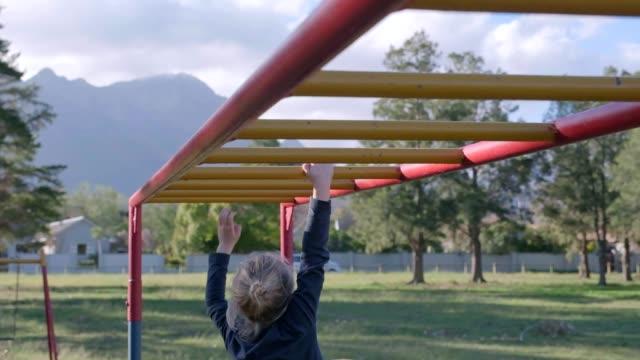 vídeos y material grabado en eventos de stock de joven jugando en el parque - estructura metálica para niños