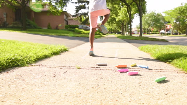 young girl playing hopscotch on suburban sidewalk. - driveway stock videos & royalty-free footage