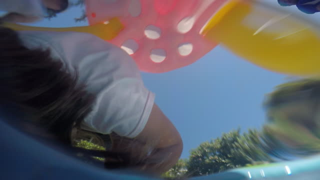 vidéos et rushes de a young girl playing in a small plastic swimming pool outdoors on a sunny day. - pataugeoire