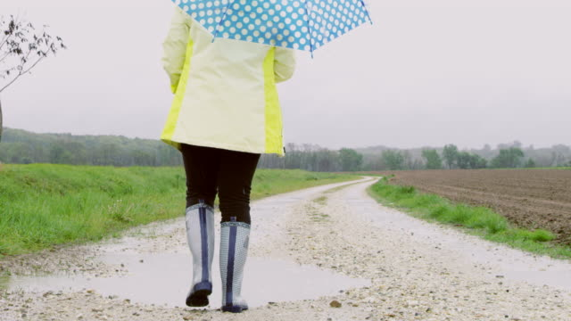slo mo young girl playing in muddy puddle - wellington boot stock videos & royalty-free footage