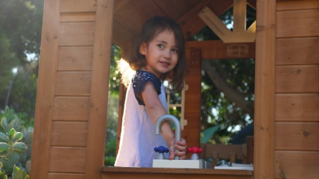 ms young girl playing in play house in backyard on summer morning - playhouse stock videos & royalty-free footage